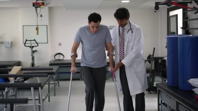 vídeos de stock e filmes b-roll de orthopedist at the hospital helping a young patient use crutches for the first time - melhoria