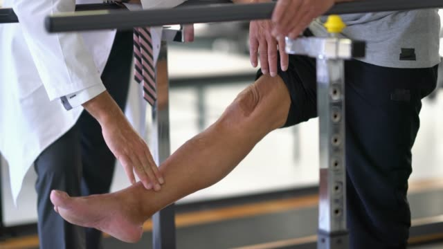 Orthopedist checking the foot of a senior patient who is supporting himself on the parallel bars while they talk Orthopedist checking the foot of a senior patient who is supporting himself on the parallel bars while they talk very seriously orthopedic equipment stock videos & royalty-free footage