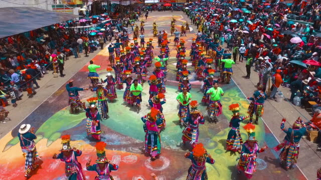 Oruro village carnival parade aerial view Colorful Bolivian folklore parade with Tinkus dancing and parading. Masterpiece of the Oral and Intangible Heritage of Humanity by Unesco. carnival celebration event stock videos & royalty-free footage