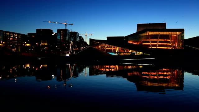 オスロ オペラハウス、夕暮れ時にその反射と都市の景観 - オペラ点の映像素材/bロール