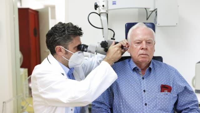 Otolaryngologist examining ear of a senior man Mature doctor examining ear of a senior patient in clinic. Senior man at check-up at otolaryngologist. ear stock videos & royalty-free footage