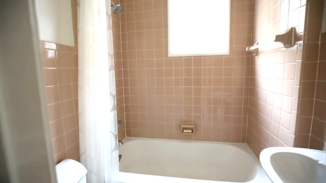 Out Dated Bathroom Push In Through Door camera moves in slowly showing and out dated bathroom with pink tiles bathroom stock videos & royalty-free footage