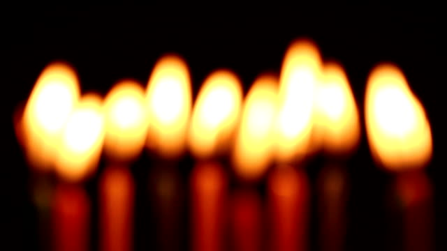 Bидео out of focus birthday candles light on isolated black