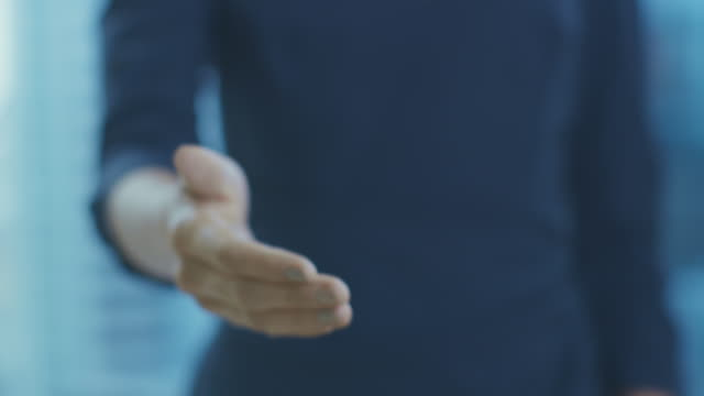 out of focus businesswoman offering her hand for a handshake. hand in focus. finalizing the deal and concluding contract with a handshake. - avvicinarsi video stock e b–roll