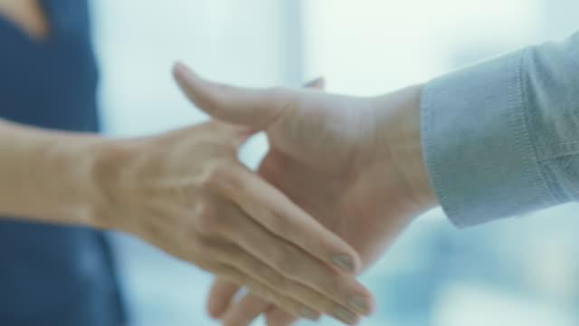 stockvideo's en b-roll-footage met out of focus zakenvrouw schudt haar hand met een zakenman. handen in focus. het finaliseren van de deal en sluiten van contract met een handdruk. - shaking hands
