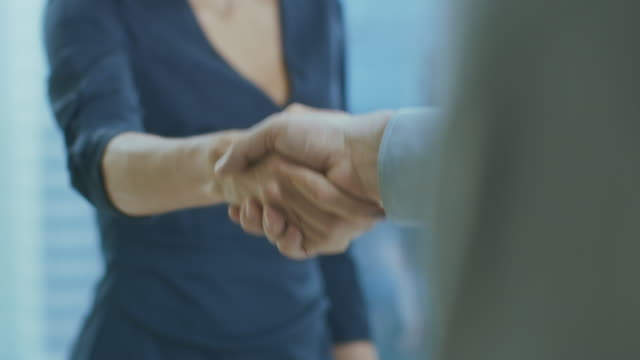 out of focus businesswoman shakes her hand with a businessman. hands in focus. finalizing the deal and concluding contract with a handshake. - fiducia video stock e b–roll