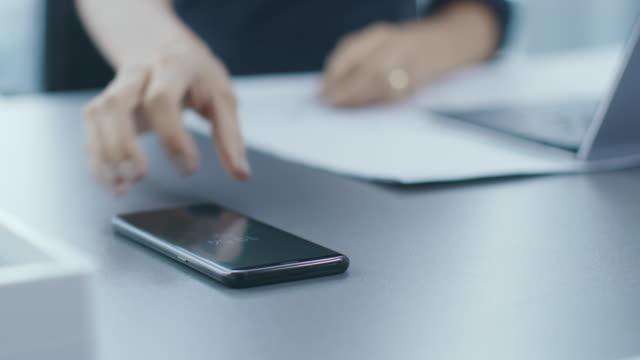 彼女のオフィス デスク手を差し伸べる彼女のスマート フォンの開始を使用してそれの女性を拾って彼女の机から携帯電話で実業家の作業の焦点のショット。携帯電話に焦点を当てます。 - 持ち上げる点の映像素材/bロール