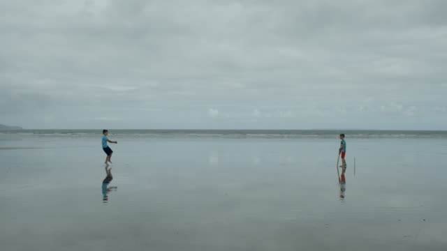 'Out'! Two young boys playing beach cricket, the bowler hits the wicket! video