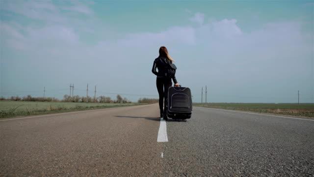 Utomhusaktiviteter resekoncept kvinna på asfaltväg med väska. Tillbaka vy video