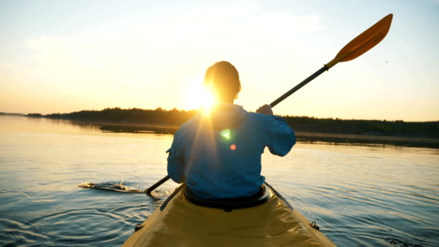 outdoor activities unity with nature, man kayaking on calm lake against sunset rays - vídeo