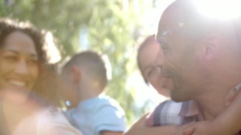 vídeos de stock e filmes b-roll de outdoor head and shoulders portrait of family in garden - felicidade
