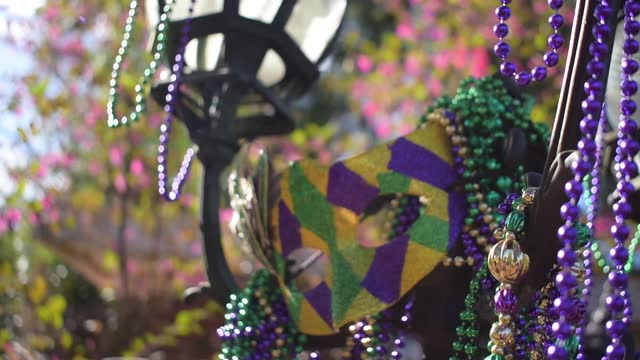 Outdoor Mardi Gras beads and mask Outdoor Mardi Gras beads and mask on light post in sunshine mardi gras stock videos & royalty-free footage