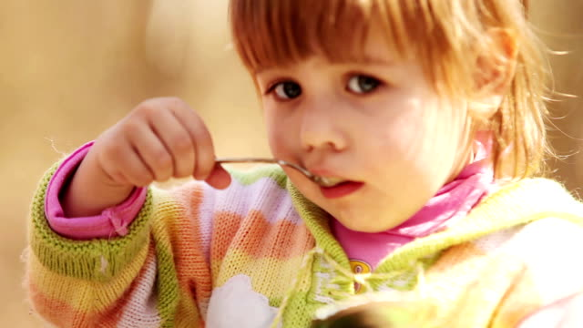 Outdoor portrait : Cute Little girl eats with spoon video