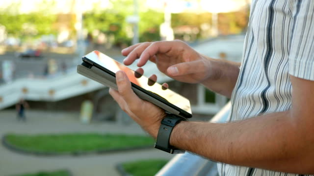 outdoor portrait of modern young man with digital tablet in the street. against the background of people walking and talking fast city life. close-up - solo bambini maschi video stock e b–roll