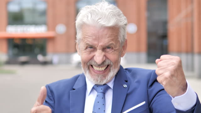 outdoor portrait of old businessman celebrating success - capelli grigi video stock e b–roll