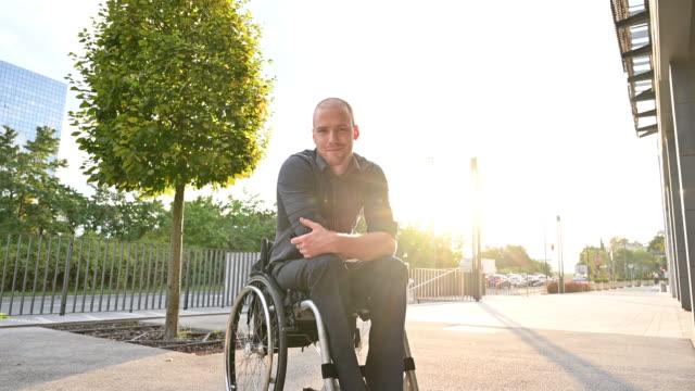 vidéos et rushes de verticale extérieure de jeune homme de sourire dans le fauteuil roulant - vue en contre plongée
