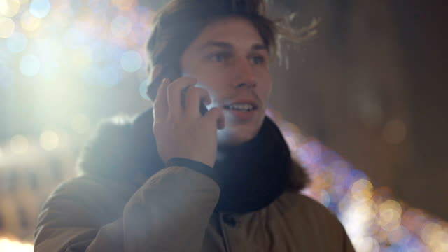 Outdoor portrait of young man using his mobile phone at night. video