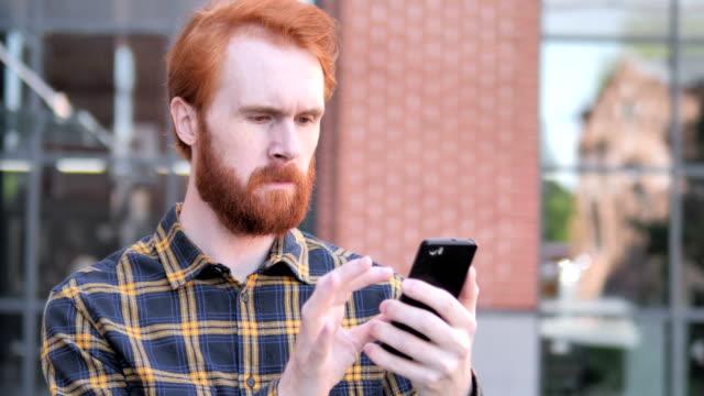 utomhus redhead skägg ung man använda smartphone - rött hår bildbanksvideor och videomaterial från bakom kulisserna