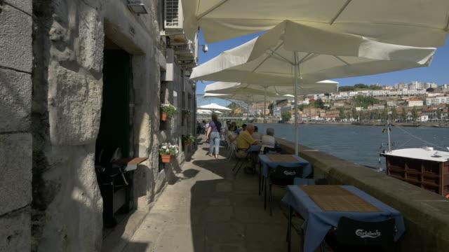 vídeos de stock e filmes b-roll de outdoor restaurant on the riverside - portugal