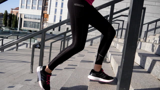vídeos de stock e filmes b-roll de outdoor shot of fit young woman running up stairs. female athlete climbing up the steps. - young woman running city
