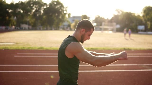 outdoor shot of young athlete male stretching his hand on a track in stadium. man wearing black t shirt and shirts. sun shines on the background - top nero video stock e b–roll