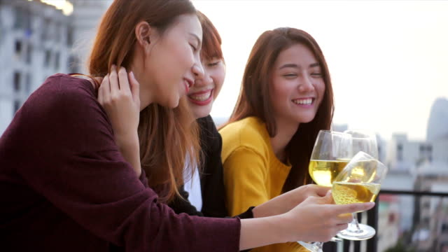 Outdoor shot of young people toasting drinks at a rooftop party. Young asian girl friends hanging out with drinks. Holiday celebration festive party. Teenage lifestyle party. Freedom and fun outdoor. video