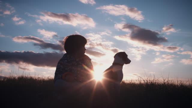 4k outdoor-silhouette von kind und hund den sonnenuntergang - nutztier oder haustier stock-videos und b-roll-filmmaterial