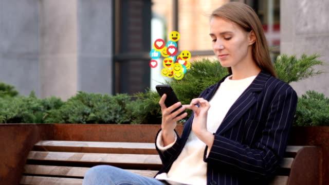 donna d'affari seduta all'aperto che usa smartphone, smiley volanti, emoji e mi piace - icona dei social network video stock e b–roll