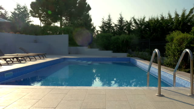 Outdoor swimming pool and empty deck-chairs video
