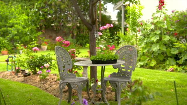 vídeos y material grabado en eventos de stock de mesa y sillas al aire libre en un hermoso parque ajardinado jardín trasero - backyard