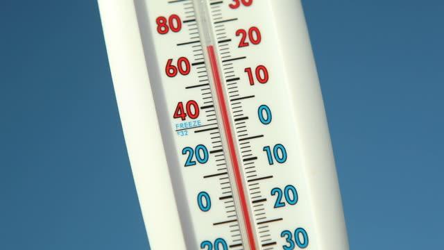 vidéos et rushes de thermomètre à affichage extérieur contre ciel bleu chute de la température - température