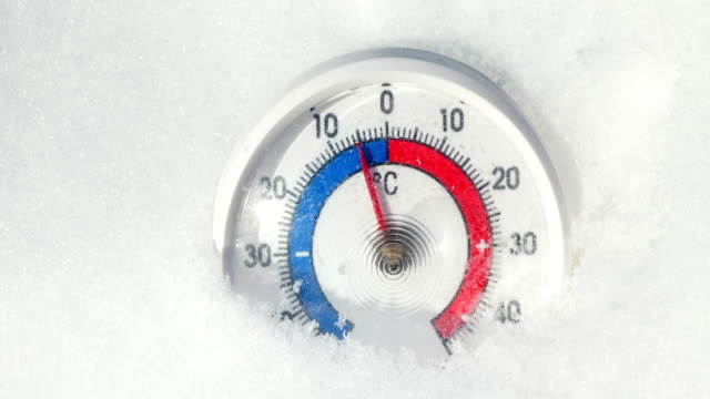 outdoor thermometer in the snow shows decreasing temperature - cold winter weather change concept - temperatura video stock e b–roll
