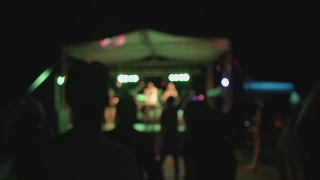 Outdoors concert at night - blurry defocused concept footage