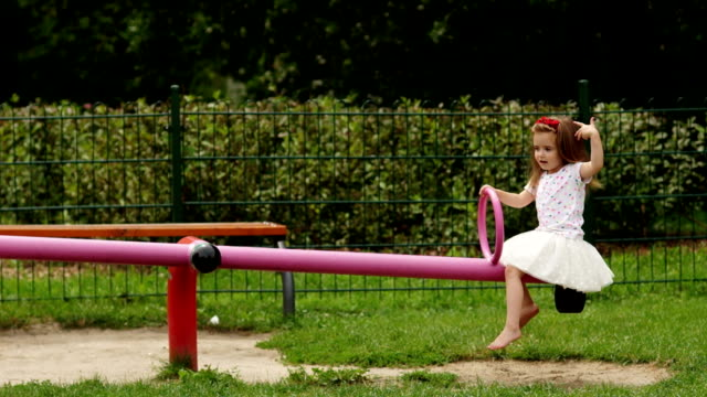 Outdoors Portrait of Cute Girl with Long Hair and Wreath of Red Flowers on the Playground During Summer Warm Day. video