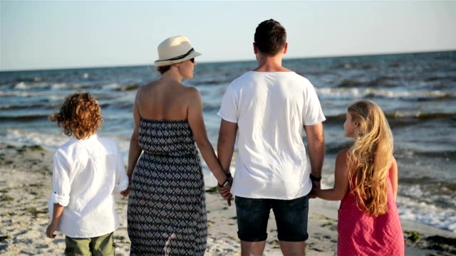 Outdoors Portrait of Mother, Father, Son and Daughter Holding Hands on the Beach During Sunny Windy Day near the Sea video