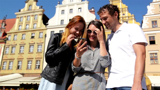 Outdoors Portrait of Three Friends Using Mobile Phone on Old Buildings Background During Sunny Summer Day video