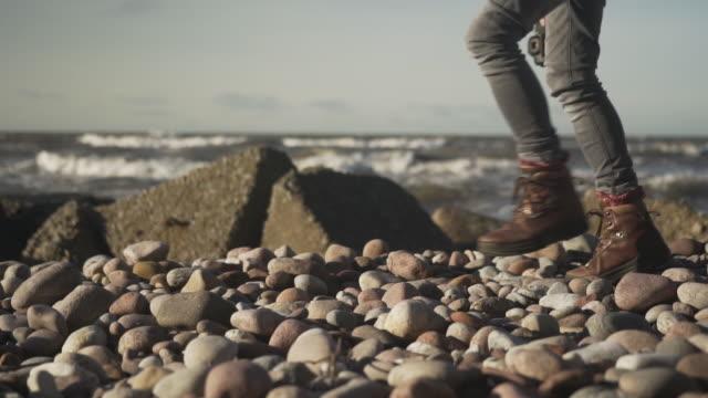 Outdoorsy photographer walking on pebble beach