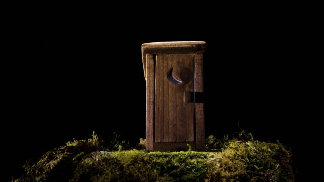 Outhouse bathroom shed miniature model motion slider shot in 4k against black background