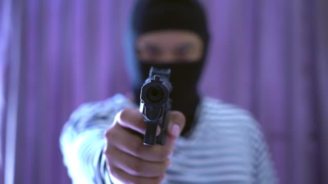 outlaw dålig människa håller en pistol pekar målet, rånare i svart huva håller en pistol och pekar på ett offer. - hotelse bildbanksvideor och videomaterial från bakom kulisserna