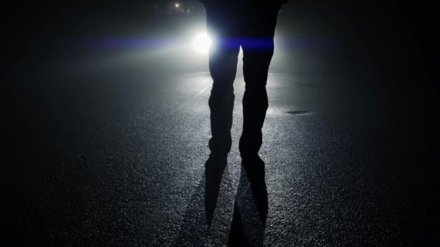 stockvideo's en b-roll-footage met contouren van de man die voor een auto in het donker. 's nachts met schaduwen en terug licht. - mist donker auto