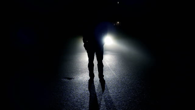 Outlines of Man Standing in Front of a Car in the Dark. At Night with Shadows and Back Light. video