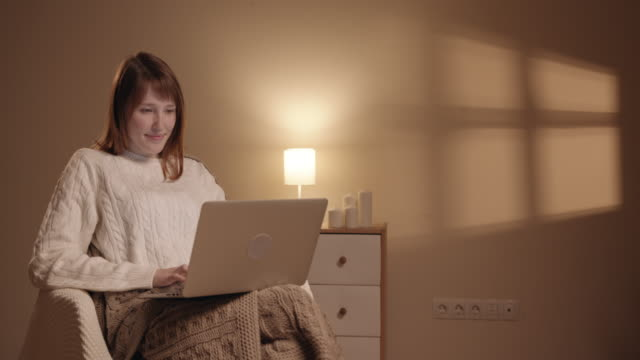 Outside the window, the street lights turn on and the room becomes bright and cozy. Girl opens notebook and is beginning to work.