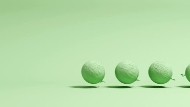 Outstanding green melon rolling after melons on green background. Minimal concept idea. 3D Animation