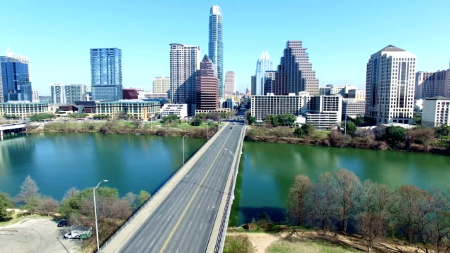 Over Congress Bridge colorful blue sky day moving towards Texas State Capitol through Austin Texas Skyline video