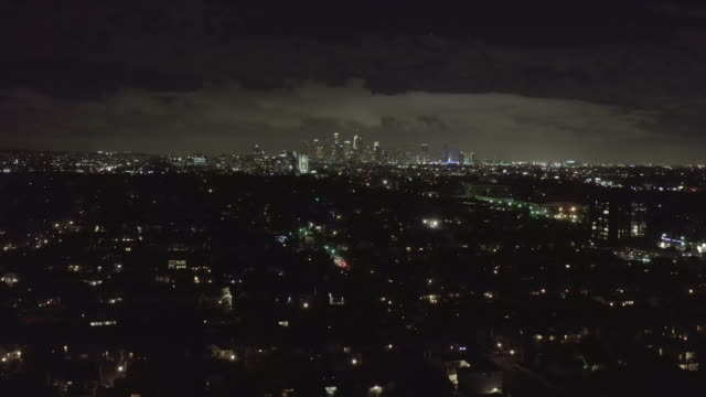 vidéos et rushes de aerial: over dark hollywood los angeles at night with clouds over downtown and city lights - californie du sud