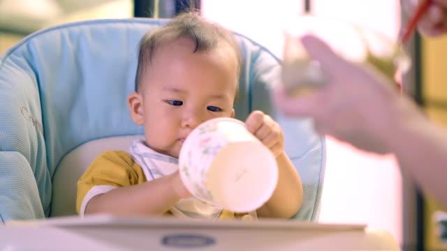 食べる以上: スプーンで離乳食を食べる赤ちゃん。 ビデオ