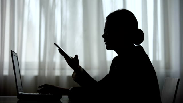 over exhausted woman talking on phone with foreign partners working on laptop - shifts call centre video stock e b–roll