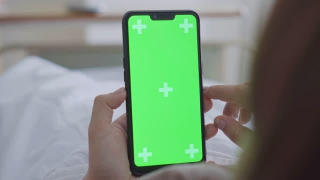 スマートフォンを使用した女性患者のオーバーショルダーショット、グリーンスクリーン - スマホ ベッド点の映像素材/bロール