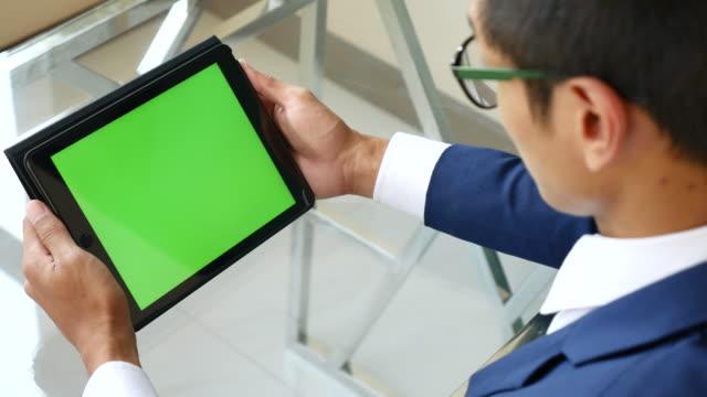 Over shoulder shot of Using digital tablet, Green screen