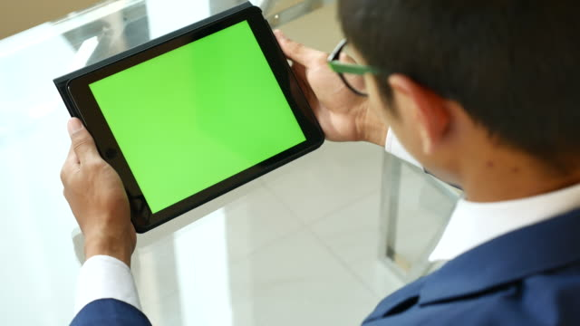 Over shoulder shot of Using digital tablet with Green screen, Chroma key video